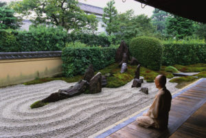 ca. 1990s, Kyoto, Honshu, Japan --- A Buddhist monk meditate beside a Zen rock garden at the Zuiho-in inside the Daitokuji Temple complex of Kyoto. --- Image by © Catherine Karnow/CORBIS